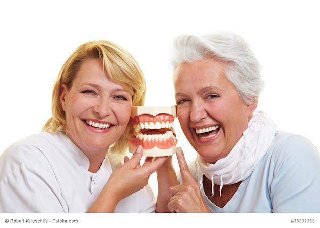 Zahnarzt und Seniorin lachen neben einem Gebissmodell