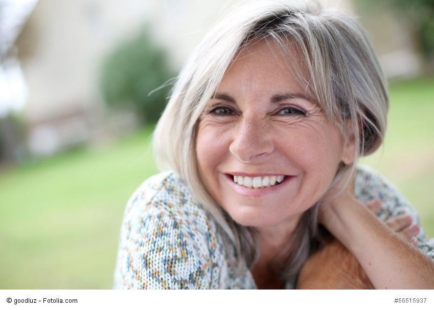 Frau schaut glücklich mit schönen und gesunden Zähnen